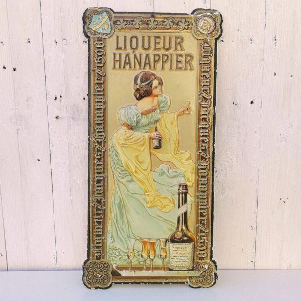 Tôle publicitaire emboutie pour la liqueur Hanappier, datant des années 1910. Représentant une femme levant son verre de liqueur pour trinquer. Des manques de peintures et rayures d'usage. Couleurs encore bien vives. Un oeillet d'accroche sur le haut. Bon état général. Dimensions : 47,5 x 24 cm