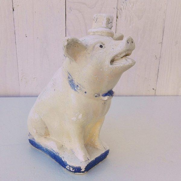 Pot à pourboire ou tirelire a casserreprésentant un cochon datant des années 60, en plâtre peint. Des éclats sur les oreilles, la bouche, les pieds,le chapeau, le noeud papillon et sur le pourtour du socle. Peinture usée. Il était posé sur le comptoir des boucherie-charcuterie. Dans son jus. Hauteur : 19 cm Dimensions socle : 6,5 x 11 cm