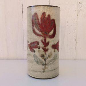 Vase rouleau en céramique par Gustave Reynaud pour le Mûrier à Vallauris. Décor à la fleur rouge. Un éclat et égrenure au col ainsi qu'un choc sous le vase. Bon état général. Hauteur : 17 cm Diamètre : 8 cm