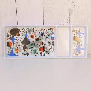 Vide poche en porcelaine sérigraphiée, à décor d'un tableau de Juan Miro. Composé de trois compartiments un grand et deux plus petits identiques. Traces d'usage. Bon état général. Dimensions : 30,5 x 12,5 cm