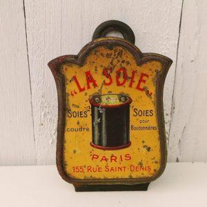 Ancienne pince publicitaire pour la soie à coudre ou la soie pour boutonnières, en tôle peinte datant des années 50. Traces de piqûres sur le devant de la pince, mécanisme de pincement fatigué. Dans son jus. Dimensions : 11 x 6 cm