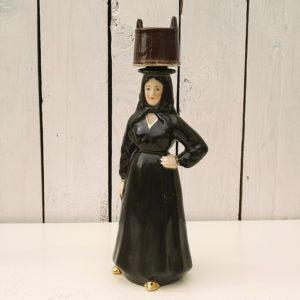 Ancienne bouteille de liqueur en porcelaine de France, représentant une femme corse vêtue de noir transportant de l'eau dans un seau. Les chaussures, poignet de manche et encolure sont dorés. Le seau fait office de bouchon, le bouchon en liège est coincé à l'intérieur et est partiellement cassé. Petits chocs sur le coté de la robe sans gravité. Je laisse l'acheteur retirer le bouchon coincé à l'aide d'une pince pour avoir le gabarit . Bon état général. Hauteur : 25 cm