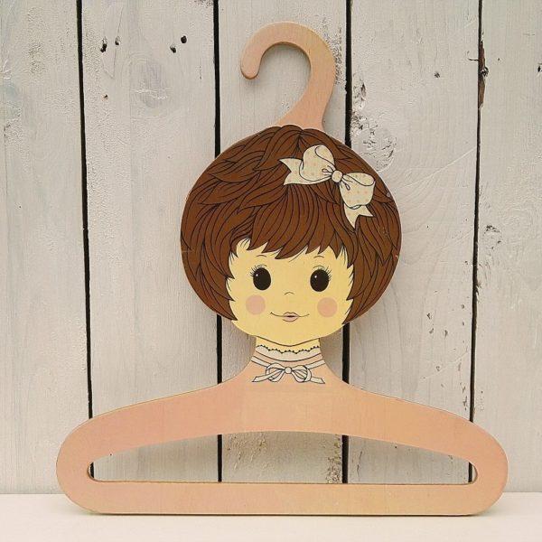 Cintre en bois datant des années 60-70, représentant le visage d'une jeune fille. de couleur rose. De la marque Goluxo . traces de rayures sur le visage Bon état. Hauteur : 35 cm Longueur : 32 cm (2 disponibles)