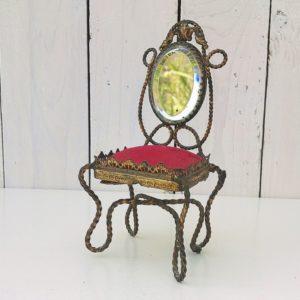 Ancien porte montre de gousset en forme de chaise de style Napoléon III. Assise en velours rouge et dossier en miroir biseauté Structure en métal torsadé doré. Le pied arrière droit a été ressoudé sur le haut et le bas. Bon état général. Hauteur : 17 cm
