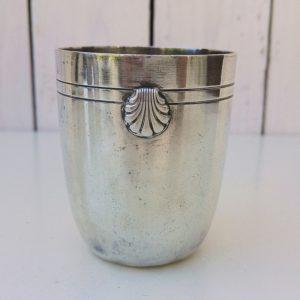 Timbale de baptême au coquillage, en métal argenté, signé Ercuis. Quelques chocs à la base de la timbale, quelques tâches d'oxydation superficielles. Rayures d'usage à l'intérieur et extérieur Bon état général. Hauteur : 7,5 cm Diamètre : 6 cm