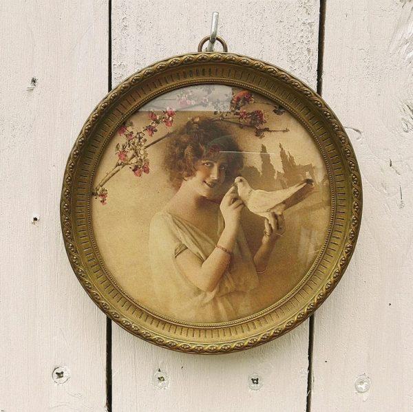 Cadre romantique de style Louis XVI au décor d'une femme à la colombe sous un arbre fruitier. De forme ronde, cerclage en laiton , verre légèrement bombé, Un anneau d'accroche sur l'arrière. Très bon état. Diamètre : 13,5 cm