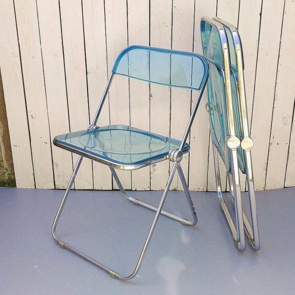 Lot de trois chaises Plia, dessinées par Giancarlo Piretti. De couleur peu commune bleue turquoise. Datant des années 70. Une légère déformation sur l'arrière d'une assise d'une chaise (sans gravité), pléxi légèrement craquelé au niveau d'une rotule d'une chaise, Corrosion plus importante sur le pied d'une chaise, rayures d'usage sur les assises et dossiers. Petites traces de corrosions sur les deux autres chaises. Bon état général. Hauteur totale ouverte : 75 cm Hauteur assise : 44 cm Largeur : 46,5 cm Profondeur : 47,5 cm Hauteur pliée : 90 cm Epaisseur fermée : 5 cm