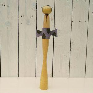 Poupée kokeshi est une poupée traditionnelle japonaise en bois originaires de la région du Tohoku. Orné d'un obi autour de la taille se finissant par un noeud à l'arrière. Traces d'usage et quelques griffures. Une éclisse sur le dessous du catogan. Bon état général. Hauteur : 37,5 cm