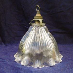 Suspensionen verre strié datant des années 50. De la marque Holophane. La particularité des verres holophane est la très bonne diffusion de la lumière. Une paillette sur le haut de la suspension à peine visible, possède sa douille d'origine Très bon état. Diamètre max : 20 cm Diamètre au col : 5,5 cm