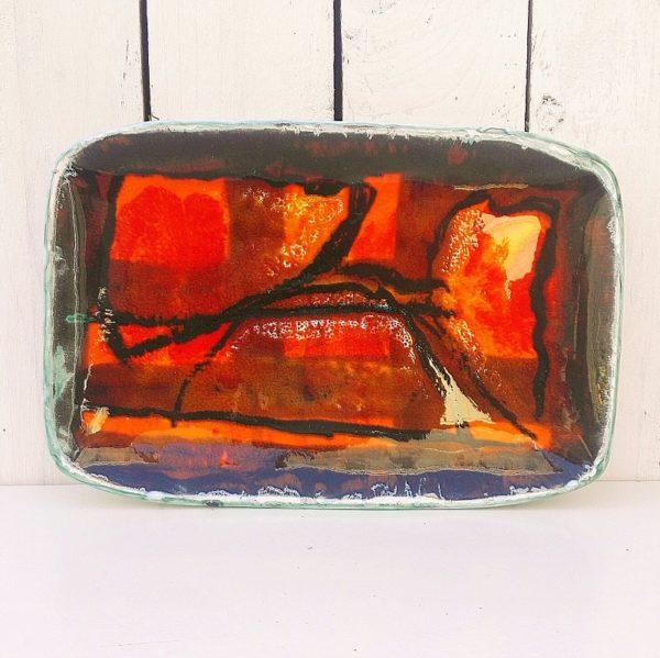 Plat en céramique datant des années 50, à décor abstrait dans les tons chauds de rouge,orange et ocre. Signé sur le dessous. Signature à identifier. Excellent état. Dimensions : 28,5 x 19 cm