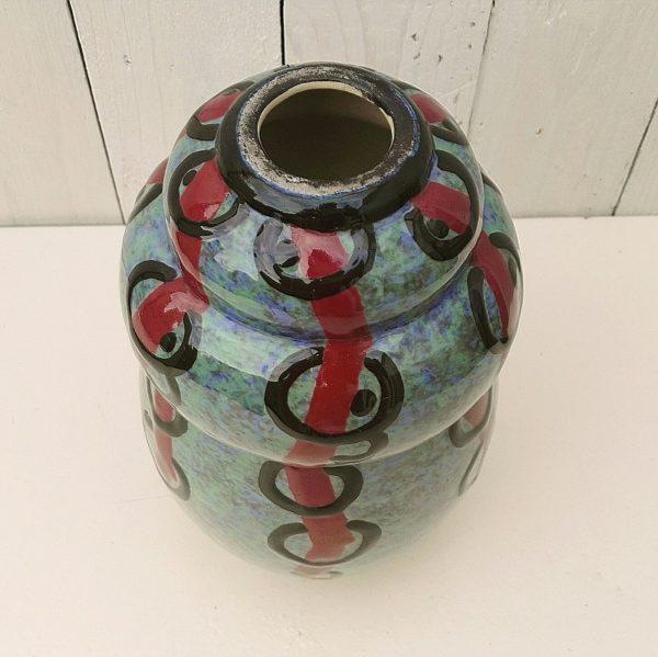 Vase annelé art déco, en céramique émaillée, créé par Louis Dage, à décor de lignes rouge traversant des anneaux noirs, belle épaisseur d'émail. Deux féles au col, signature sur le bas du vase Hauteur : 24,5 cm