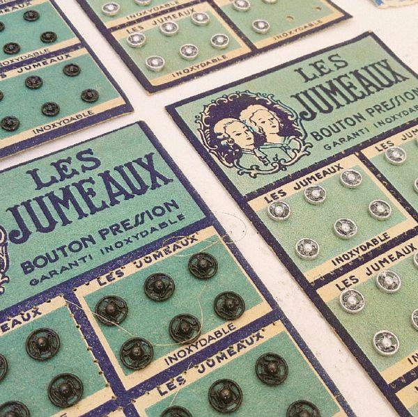 Ancienne boite de la mercerie Wallaert frères de Lille contenant des plaquettes de boutons pressions de la marque jumeaux pour la plupart. Plusieurs tailles et deux coloris inox et noir. Tous les boutons contenus dans la boite sont mâles. Boite jaunie et déformée. Les plaquettes de boutons pressions sont jaunies, quelques déchirures. Dans leur jus.