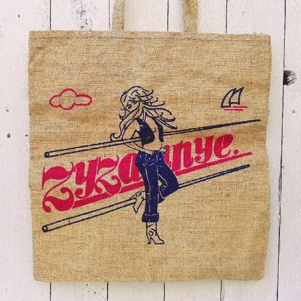 """Ancien sac ou tote bag en toile de jute datant des années 60. Impression d'une femme en jean sur le dessus et d'une marque """" Zyzanye"""". Sac vintage incroyablement tendance. Quelques petites taches sur le sac. Les couleurs sont très vives. Bon état général. Dimensions sans les bandoulières : 40 x 38,5 cm"""