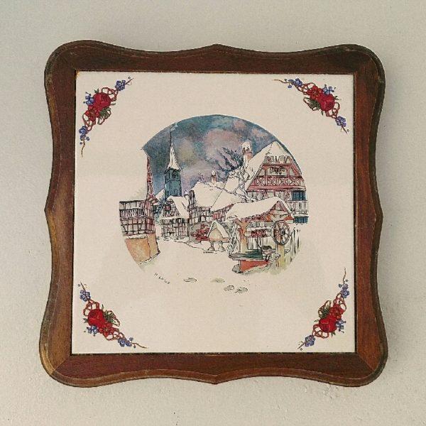 Dessous plat en faïence de Sarreguemines, Obernai représentant un village sous la neige. Signé Henri Loux. Quatre pieds en bois tournés en dessous. Petites traces de rayures d'usage sans gravité. Très bon état. Dimensions : 24,5 x 24,5 cm