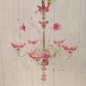 Lustre en verre de Murano, modèle casanova, de couleur transparente et rose poudré. Cinq feux de lumière enchassés dans des corolles de fleurs. Composé de trois feuilles style acanthe montantes ,trois fleurs montantes. et trois feuilles acanthes descendantes. Manque deux feuilles tombantes, Une feuille tombante et une fleur sont a recaler dans leur bouchon respectif qui sont présents. Très charmant et élégant. Un travail de précision du verre. Bon état Hauteur avec chaînette de suspension : 65 cm Hauteur sans chaînette de suspension : 50 cm Envergure : ~45 cm
