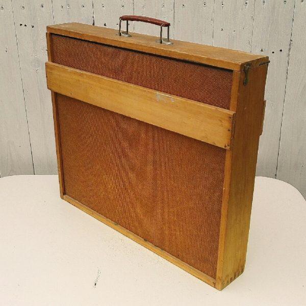 Malette ou valise de transport en bois pour toile de peintre, couvercle avec poignée rabattable muni de crochet de fermeture. Six glissières pour maintenir les toiles. Traces de rayures, petites tâches. Bon état général. Dimensions : 41 x 47,5 cm Profondeur : 8,5 cm
