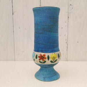 Vase en céramique sur pied douche par Jean de Lespinasse. Frise à motif de fleurs. Un micro défaut de cuisson sur le pied. Excellent état. Hauteur : 17 cm