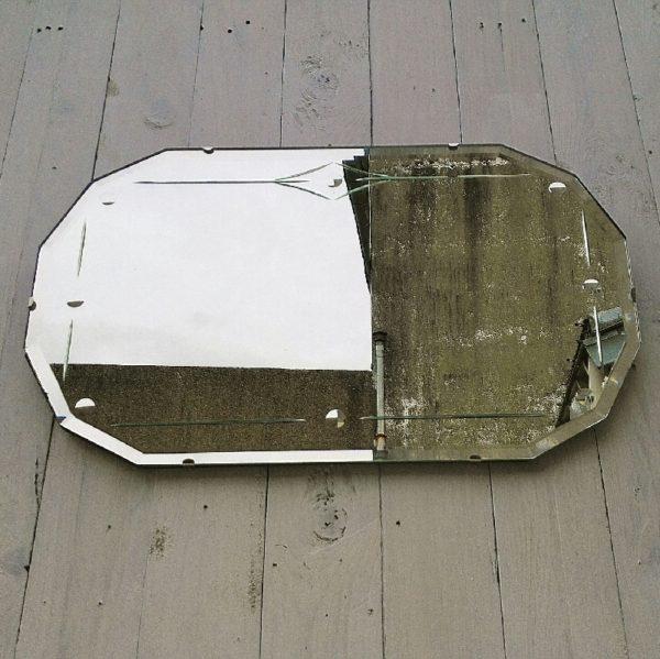 Ancien miroir datant des années 50, très épais avec un effet ciselé. Il est fixé sur une planche elle même très épaisse. Très beau travail de qualité. Possède sa chaîne d'accroche sur l'arrière. Très lourd. Quelques rayures d'usage sur le miroir sans gravité. Excellent état. Dimensions : 56 x 33 x 1,5 cm