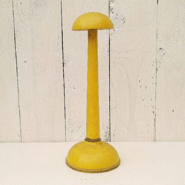 Porte chapeau ancien en bois peint de couleur jaune moutarde. Liseré doré sur le contour du socle et sur le bas de la tige. Traces d'usage et manques de peinture. Bon état général. Hauteur : 27 cm