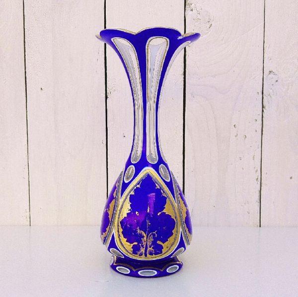 Vase à facette en cristal de bohème, overlay. De couleur bleu orné de dorures. Les dorures sont partiellement effacées sur le rebord et sur certain motifs dans les cartouches. Une paillette sur le dessous de la collerette. Bon état général. Hauteur : 21,5 cm
