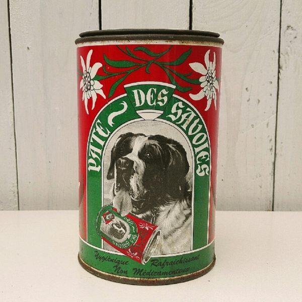 Ancienne boite en tôle peinte pour les pates des Savoies. Décor représentant un chien Saint-Bernard avec cette boite autour du cou. Quelques petits manques de peinture, traces de corrosions sur le couvercle et sur le contour bas. Un petit enfoncement sur le haut de la boite. Bon état général Hauteur : 17 cm Diamètre : 10 cm