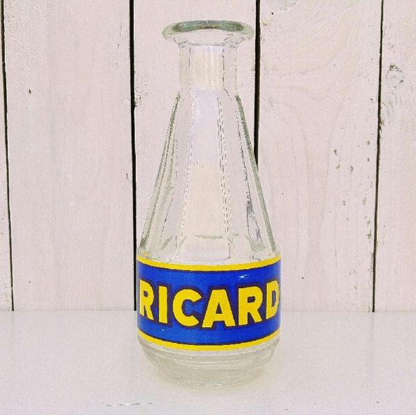 Ancienne carafe publicitaire en verre, sérigraphiée Ricard en jaune et bleu. Datant des années 50-60. Quelques petits manques sur la sérigraphie sans gravité. Très bon état. Hauteur : 20 cm