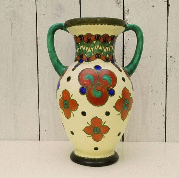Vase en céramique hollandaise art déco, à décor de fleurs et d'entrelacs. Céramique verte à l'intérieur et sur les anses. Signé sur le dessous : Magda royal, zuid Holland, WB, gouda 4031. Excellent état. Hauteur : 25 cm Diamètre col : 11 cm