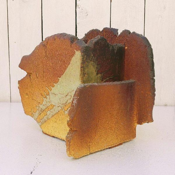 Beau vase Saint Maudez en grès à la forme architecturé dans les tons feu. Aspérités et cassures voulues par l'artiste. très design et tendance. Signé sur le dessous, trois patins de feutre sous le vase. Très bon état Hauteur : 20,5 cm Longueur max : 17 cm Largeur max : 18 cm