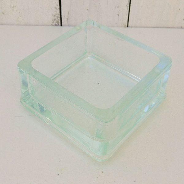 Vide poche en verre épais Lumax, à bords hauts. Servait dans les aménagements intérieurs de Le Corbusier et Charlotte Perriand. Rayures d'usage . Bon état général. Hauteur : 6 cm Dimensions : 11 x 11 cm
