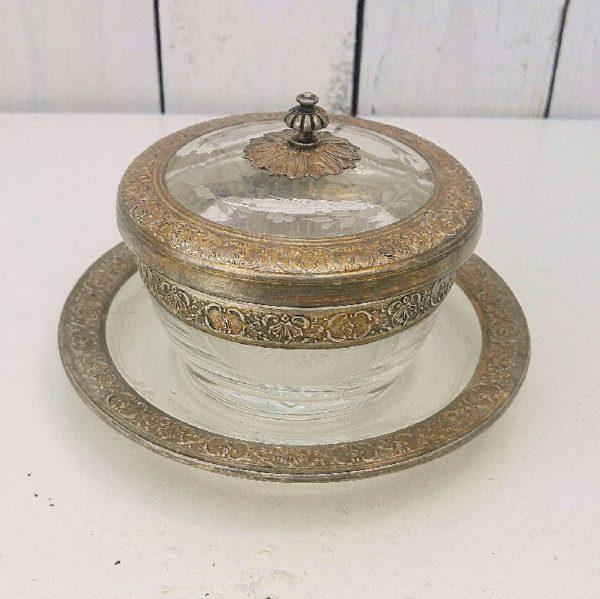 Confiturier en cristal datant du XIXe gravé d'une frise florale sur le couvercle, d'une étoile et d'une frise simple sur le dessous. Le couvercle, la coupelle et le contenant sont cerclés d'une frise en vermeil. La poignée du couvercle est aussi en vermeil. Poinçons minerve sur le vermeil. Excellent état. Hauteur avec couvercle : ~9,5 cm Diamètre coupelle : 14 cm