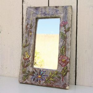 Ancien miroir en céramique de vallauris, signé sur l'arrière à identifier. Décor floral sur le pourtour. Un manque à l'arrière. Un éclat sur le coin en bas à gauche. Une accroche pour le fixer au mur. Bon état général. Dimensions : 25 x 16 cm
