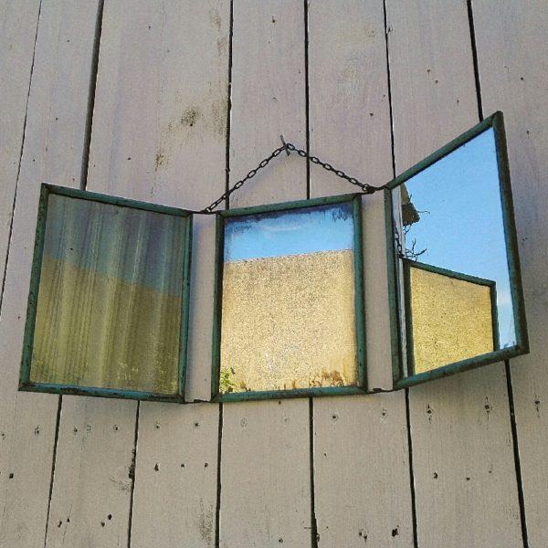 Miroir triptyque de barbier datant des années 50 en métal de couleur bleue, une chaînette permet de le suspendre. . L'arrière est piqué et taché, trace de corrosion. Les miroirs au mercure sont piqués ce qui leur confère un certain charme Dans son jus Dimensions d'un miroir : 16,5 x 21,5 cm Dimensions déployé : 54 x 21,5 cm