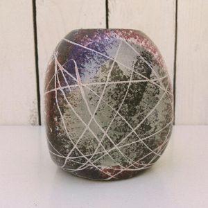 Vase de forme organique en céramique, à décor de scarifications dans les tons prune, noir et vert céladon effet moucheté. Deux égrenures sur le col. Bon état général. Hauteur : 13,5 cm