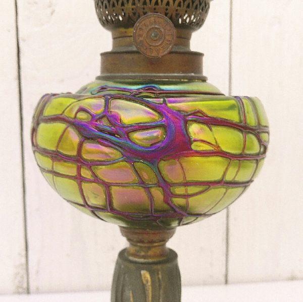 Lampe à pétrole Loetz d'époque art nouveau, pied en régule à décor de feuillages et de fruits. Réservoir en verre irisé dans les tons jaunes et verts avec relief de verre violet en double couche. Réservoir en très bon état général . Bon général. Hauteur : 28 cm Diamètre réservoir : ~13,5 cm