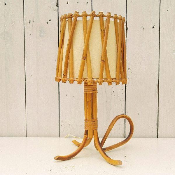 Pied de lampe vintage en rotin datant des années 50-60. Tripode et possède une poignée. Prise d'origine mais l'interrupteur à été changé. Bon état. Hauteur : 31 cm diamètre abat-jour : 14 cm