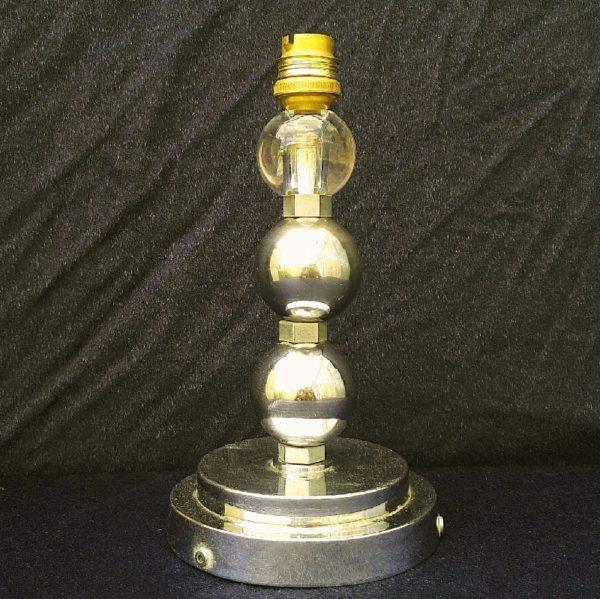 Pied de lampe art déco, composée d'un socle et deux boules en aluminium chromé et se terminant par une boule en verre épais.La lampe est à électrifier. Rayures d'usage sur le socle et le s boules en aluminium. Bon état général. Hauteur : 22 cm
