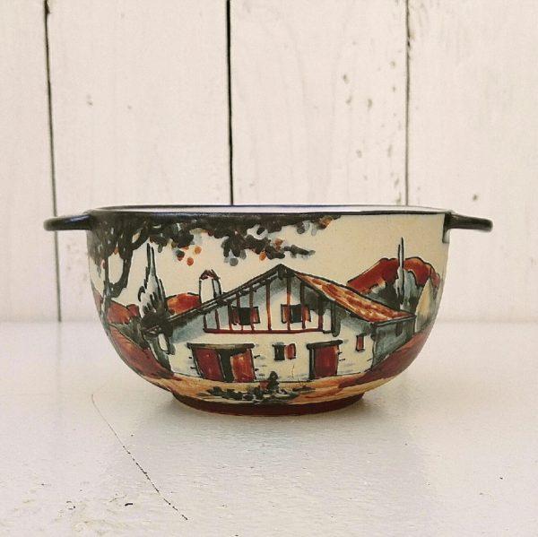 Bol à oreille provenant de la célèbre poterie de Ciboure, à décor d'une bergère dans les montagne et d'une maison typiquement basque. Signé sur le dessous C.Fischer. Un défaut de cuisson sur le col. Très bon état. Hauteur : 7 cm Diamètre : 12 cm