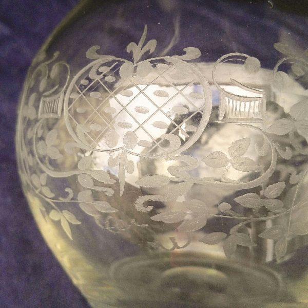Carafe en verre soufflé transparent à décor de guirlandes de feuillage et une frise sur le goulot, le tout dégagé à l'acide , datant des années 50. Elle sera d'un plus effet sur votre table. Petite traces de calcaire sur le haut du goulot Très bon état. Hauteur : 23 cm
