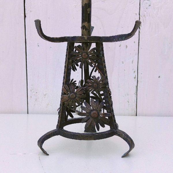 Pied de lampe art nouveau tripode en fer forgé martelé. Décor de fleurs sur le pied. Traces de corrosion superficielle, ne possède pas son globe. Dans son jus. Hauteur totale avec douille : 21,5 cm