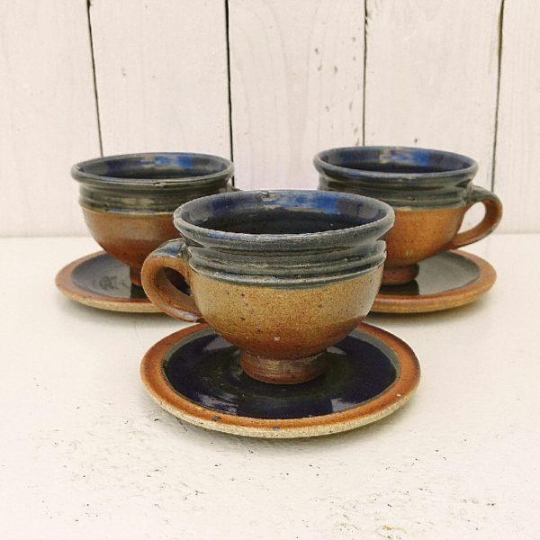 Lot de trois tasses à café avec leurs sous tasses, en grès pyrité émaillé bleu sur l'intérieur, datant des années 60, par Pierre Digan à La borne. Une égrenure sur le col d'une tasse, et des défauts de cuisson sur le col des deux restantes. Bon état général. Hauteur tasse : 7,5 cm Diamètre tasse : 9 cm Diamètre sous tasse : 12 cm